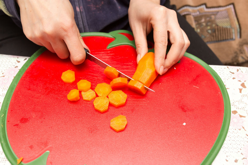 Slicing carrots on red cutting board