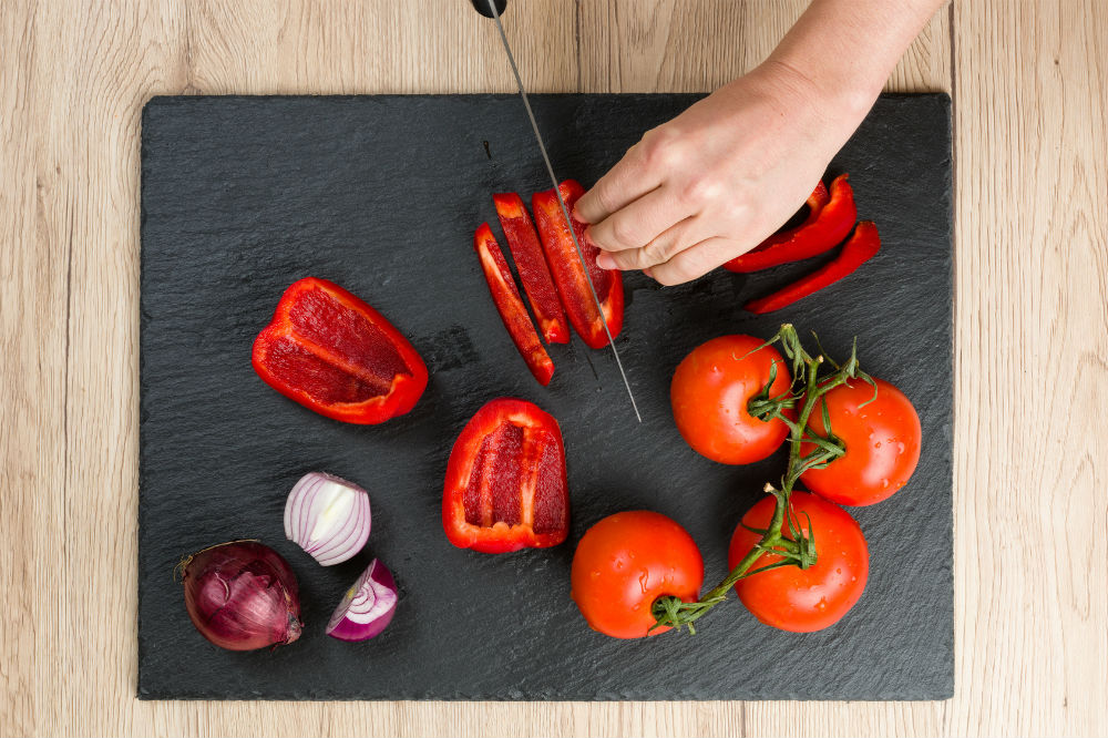 Slicing red chili on black cutting board