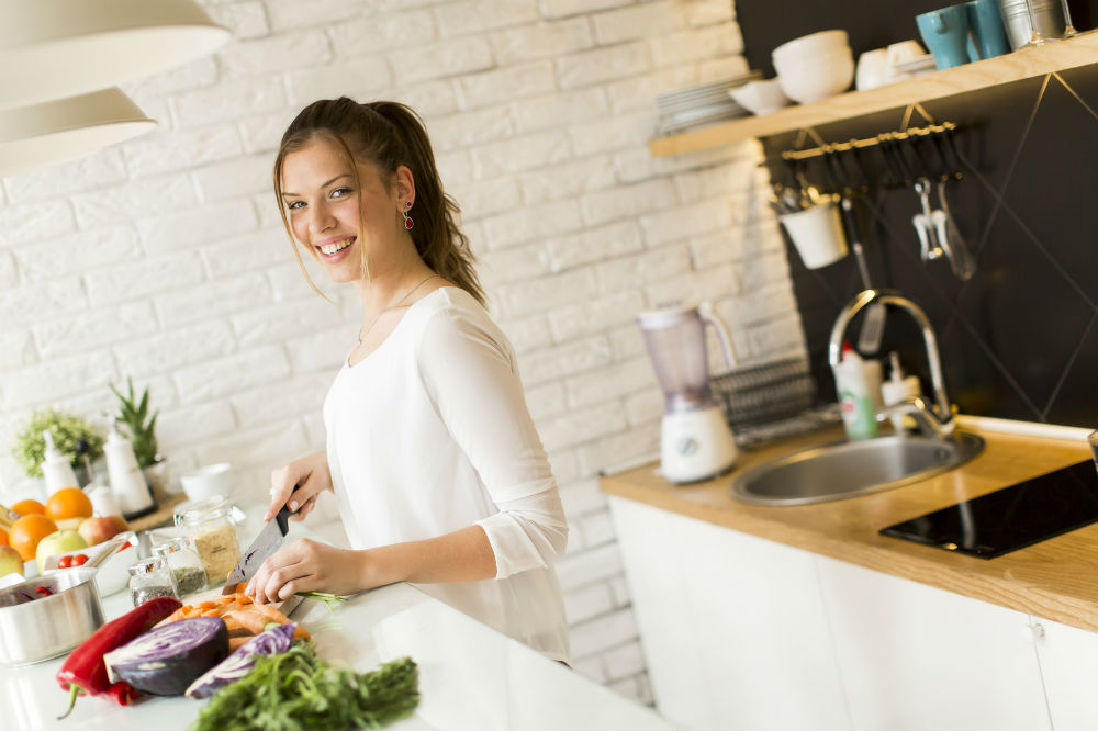 woman holding a knife cutting vegetables