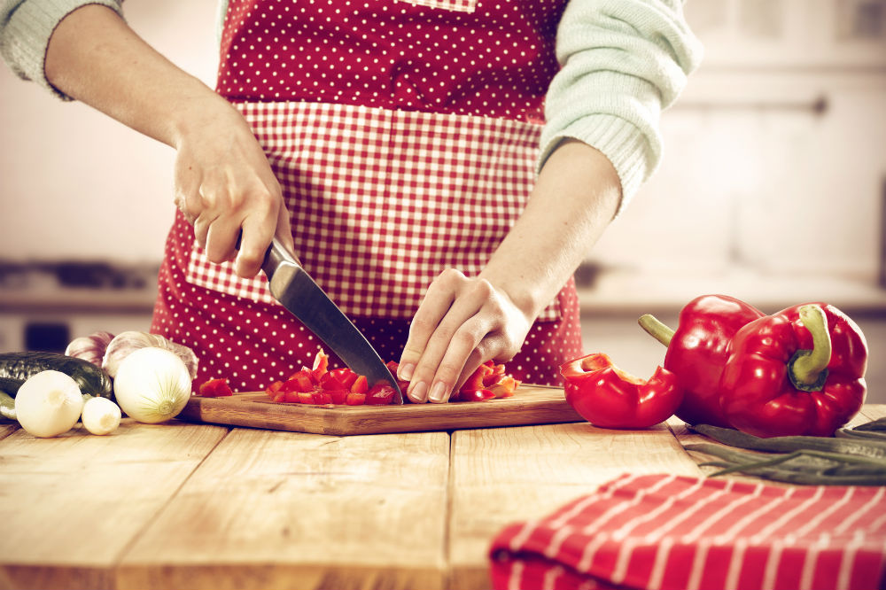 Woman with knife slicing red bell pepper using cutting board