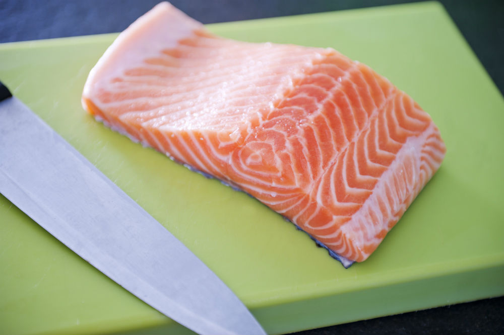 sliced salmon and knife of cutting board