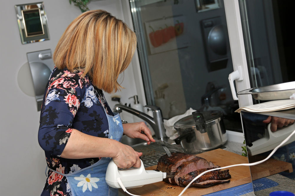 Woman using corded electric knife