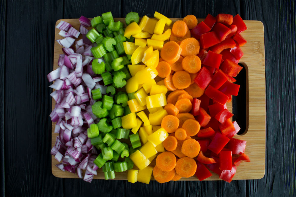 Assorted cut vegetables on a bamboo cutting board