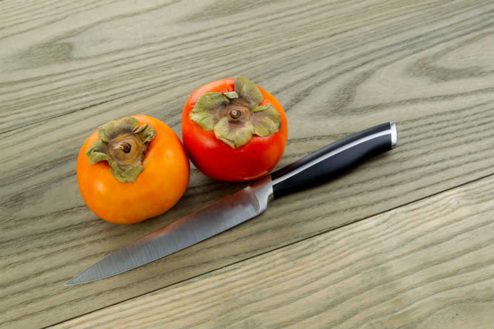 2 fresh persimmons with knife on a table